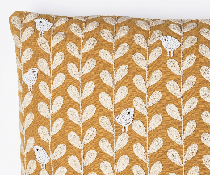 Yellow cushion hand embroidered with white beaded birds and foliage
