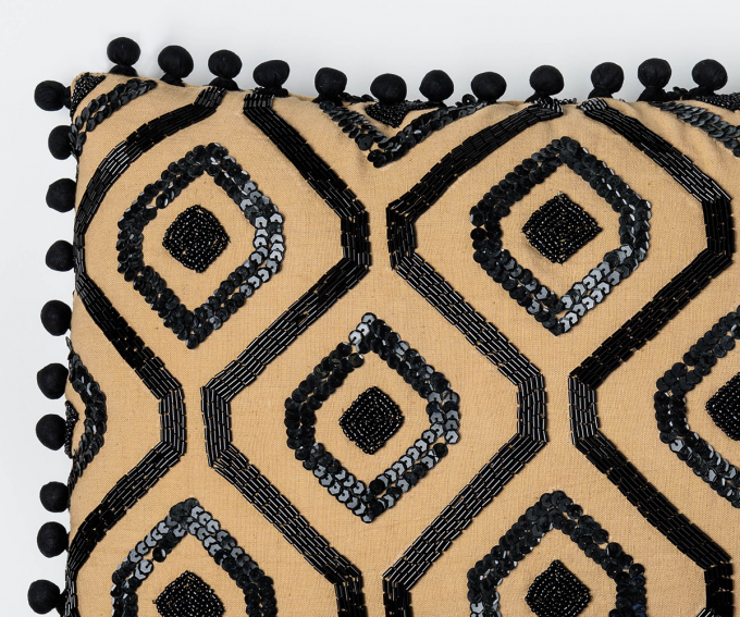 Gold linen cushion with black sequins and pompom trim.